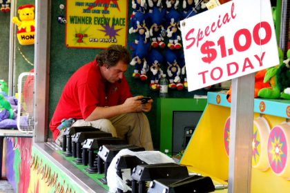 It's a slow day at the fair and a game host plays his own game while waiting for a customer.