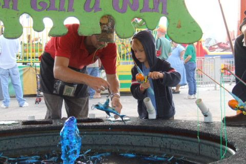 This young boy intently fishing for a prize from a pond of blue water at the Anderson County Fair, SC