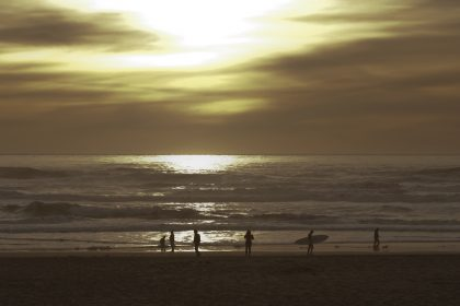 Surfer with a surf board walking on the beach at sunset in San Francisco, California
